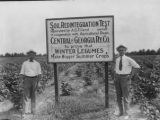 A. G. Eiland, the owner, stands by his sign with J. F. Jackson, agricultural agent, on the right