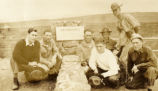 Everett Leavins and six other soldiers grouped around the sign at Halemaumau Fire Pit in Hawaii in...